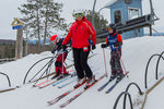 A woman with two kids skiing off chairlift