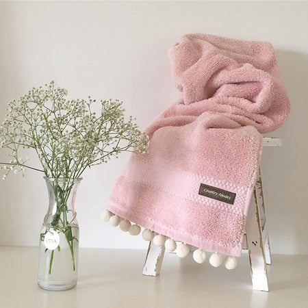 Towel with pompoms