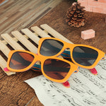 Pair of orange wood and layered skateboard wood sunglasses frame with Grey and brown lenses