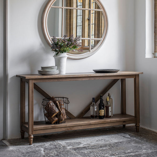 The Rural Trestle Table Smokey Oak situated in a room with large mirror and accessories