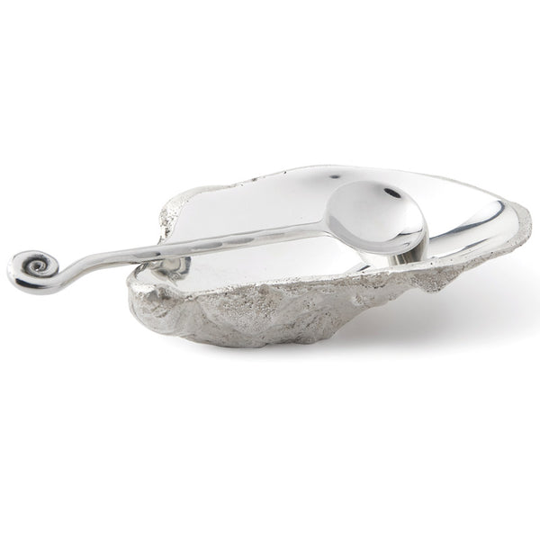 Silver oyster shell with spoon in silver metalon white background