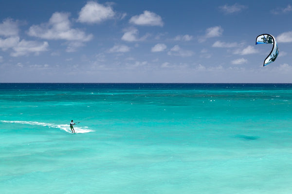 A picture of a clear blue sea with someone kiteboarding