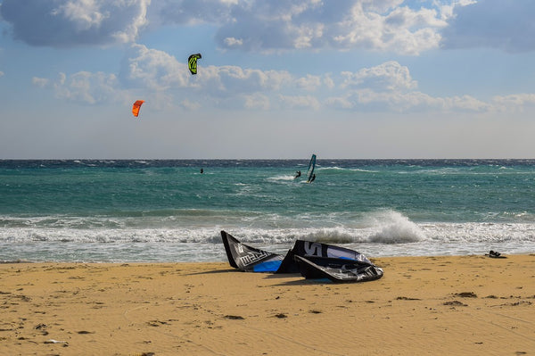 the sea with a kiteboard resting on the sand