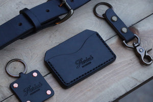 Black handmade leather accessories with brass keyring and copper rivets on wood