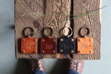 Black, brown and russet handmade leather key fobs with brass keyrings and copper rivets on wood