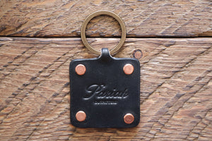 Black handmade leather key fob with brass keyring and copper rivets on wood
