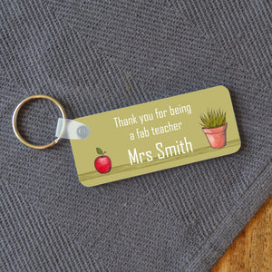 "Personalised green key ring with a design which includes an illustration of an apple and a pot plant, and a message which reads ""thank you for being a fab teacher Mrs Smith"""