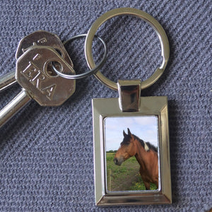 A personalised metal keyring in a rectangular shape featuring a personal photo