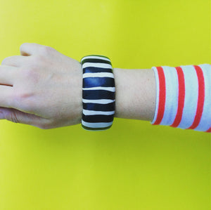 View of handmade black and white striped porcelain bangle being worn on wrist, with yellow background