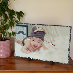 A personalised rectangular slate clock with a photo of a baby printed on it