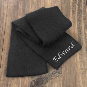 A personalised black knitted scarf with white embroidery