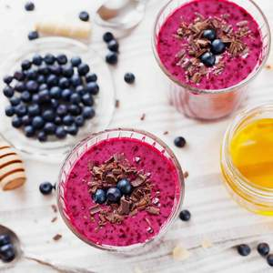 Fresh berry smoothie decorated with grated chocolate, raw honey and blueberry
