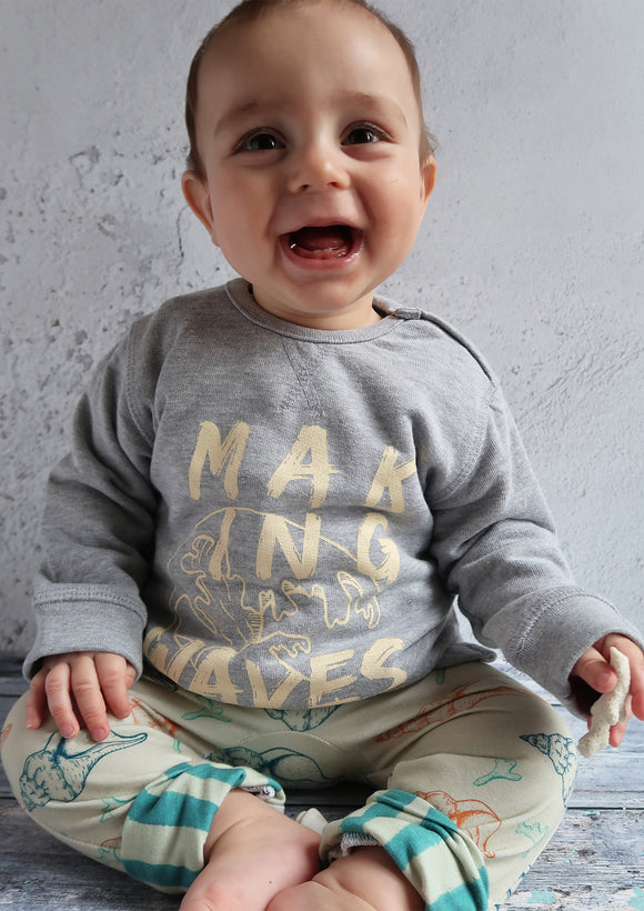 smiling baby wearing grey slogan sweatshirt