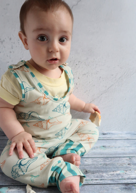 baby boy in seashell print dungaree romper
