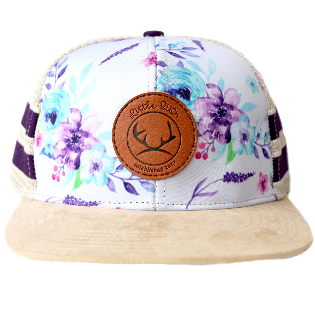 White floral hat with a leather circle patch and with purple stripes and purple flowers with a suede brim