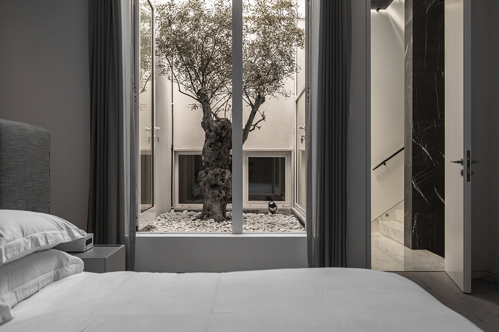 bedroom in grey tones with view to the courtyard