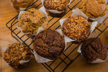 A variety of gluten free muffins, including apple pie, peanut butter dark chocolate, and banana coconut.