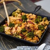 A cast iron skillet of blackened chicken with roasted broccoli, and a mixture of cauliflower rice, sun-dried tomatoes and a sauce prepared with carrots, onions, squash that has been pureed with coconut milk.