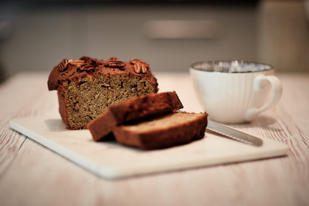 Freshly baked coffee maple and pecan banana loaf. Sliced on a chopping board next t a freshly brewed coffee