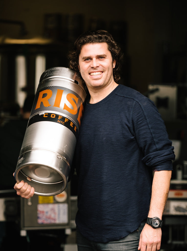 Man carrying keg of organic, non-GMO RISE nitro cold brew coffee - RISE Brewing Co.