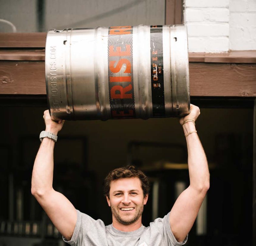 Man lifting keg of RISE nitro cold brew coffee - RISE Brewing Co.